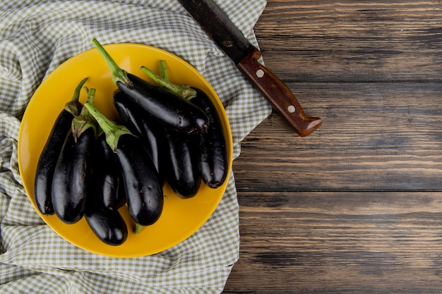 Top view of eggplants in plate with knife on cloth on left side and wooden background with copy space