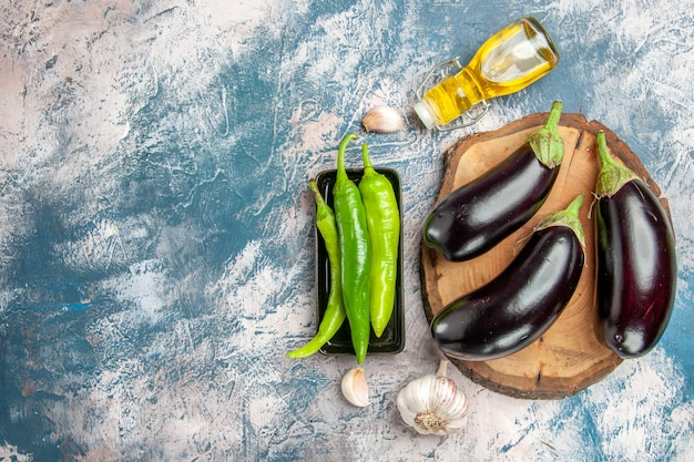 Top view eggplants on tree wood board hot peppers on black plate garlic oil on blue-white background