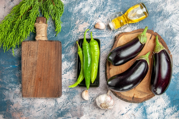 Top view eggplants on tree wood board hot peppers on black plate garlic oil chpping board on blue-white background