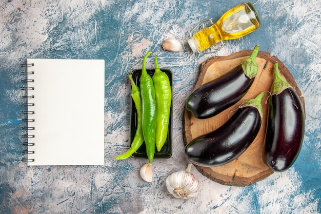 Top view eggplants on tree wood board hot peppers on black plate garlic oil a notebook on blue-white background