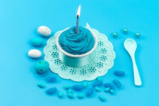 Una vista dall'alto uova e caramelle colorate con candela su caramelle alimentari blu e colorate