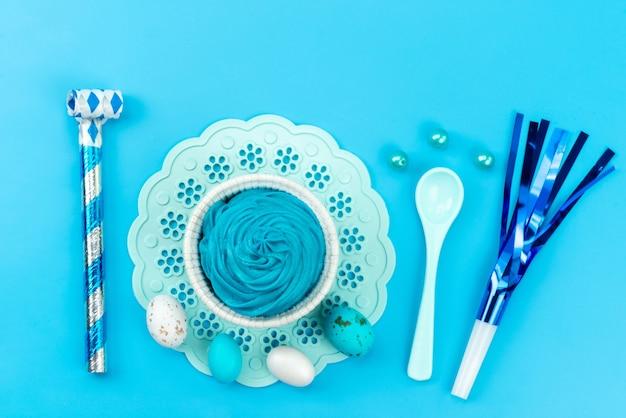 Una vista dall'alto uova e decorazioni blu e bianco, insieme a blu, dessert su blu, celebrazione della festa del regalo di compleanno