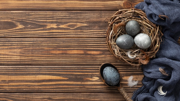 Top view of eggs for easter in bird nest with textile and copy space
