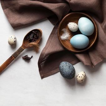 Vista dall'alto di uova di pasqua sul piatto con cucchiaio di legno e piume