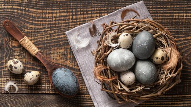Vista dall'alto di uova per pasqua nel nido di ramoscelli con cucchiaio di legno e piume