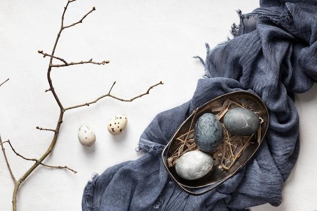 Vista dall'alto di uova per pasqua con tessuto e ramoscello