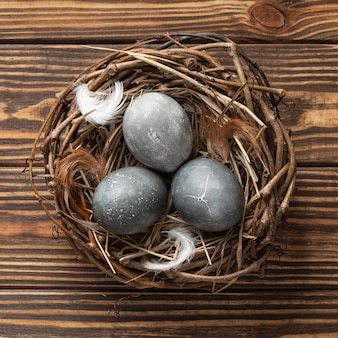 Top view of eggs for easter with feathers in bird nest