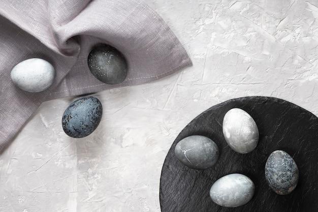 Vista dall'alto di uova di pasqua con ardesia e tessuto