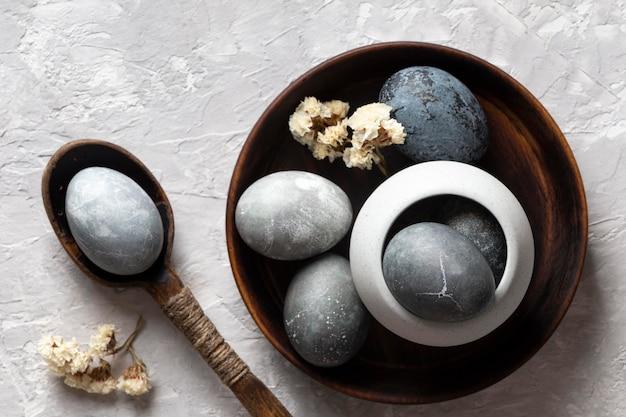 Vista dall'alto di uova di pasqua con cucchiaio e piatto di legno