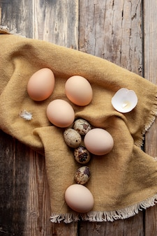 Top view eggs with broken one on cloth and dark wooden background. vertical