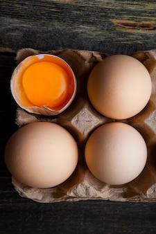 Top view eggs with broken one on dark wooden background. vertical