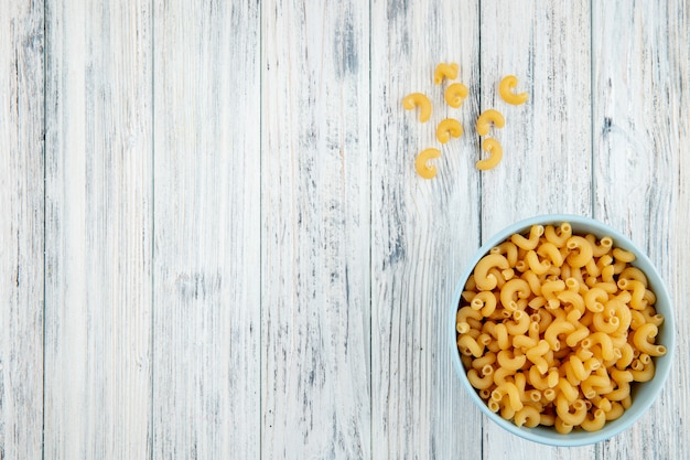 Top view elbow macaroni pasta in bowl on the right with copy space on white wooden background