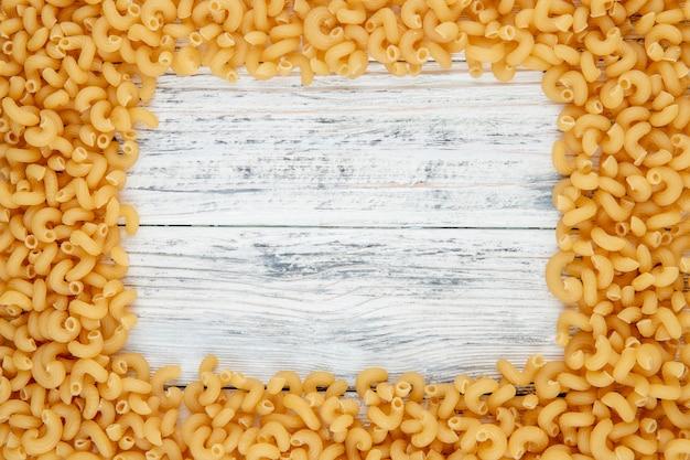 白い木製の背景にコピースペースを持つ平面図肘マカロニパスタ