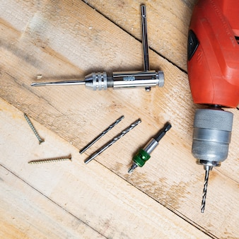 Vista dall'alto di un trapano elettrico, chiodi e altre attrezzature di riparazione su una superficie di legno
