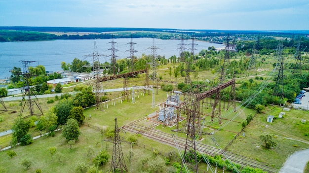 Top view of electricity pylons and high-voltage power lines on the green grass on the background of the river.