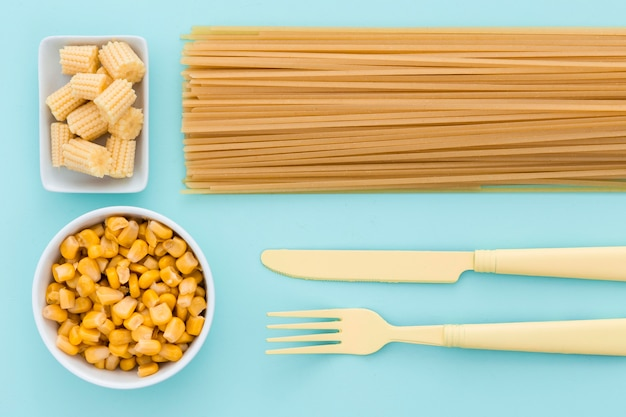 Top view elegant cutlery with pasta and corn