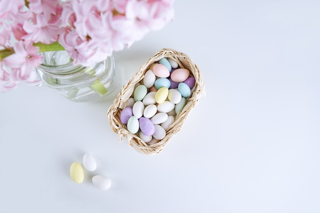 Top view of elegant hyacinth flower in vase with easter eggs candies in basket on white