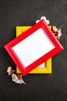 Vista dall'alto eleganti cornici con angoli gialli e rossi su superficie grigio scuro ritratto famiglia regalo foto regali colore amore