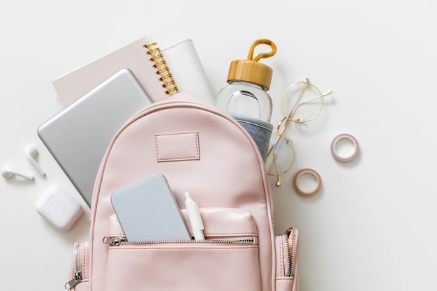 Top view elegant pink student backpack full of supplies isolated. back to school concept