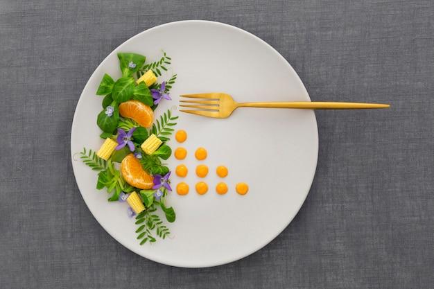 Вид сверху элегантная тарелка с золотой вилкой