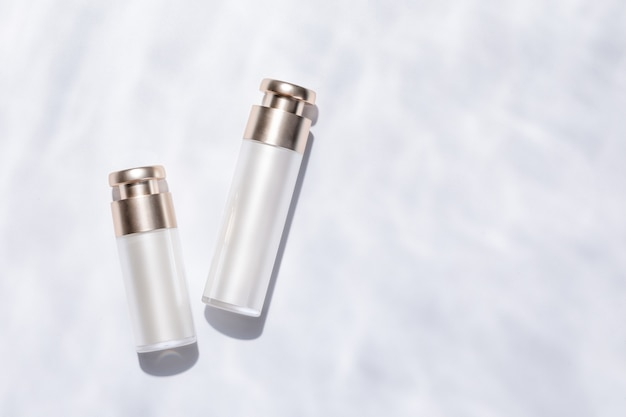 Top view of elegant skincare bottles on a white textured surface