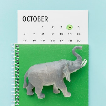 Top view of elephant figurine with notebook and calendar for animal day