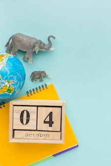 Top view of elephant figurines with planet earth and notebook for animal day