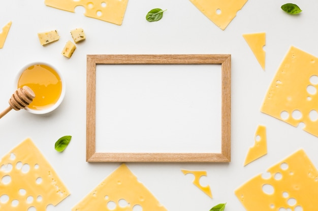 Top view emmental cheese slices with honey and wooden frame
