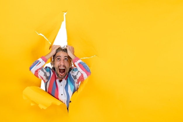 Top view of an emotional angry and exhausted young guy through a torn hole in yellow paper