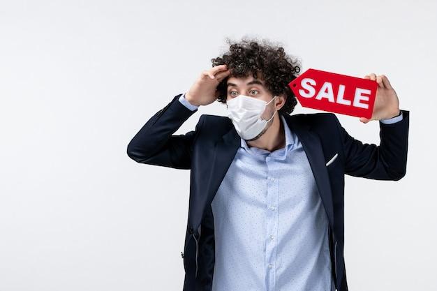 Vista dall'alto di un uomo d'affari emotivamente confuso in tuta e che indossa la sua maschera che mostra l'iscrizione di vendita su sfondo bianco