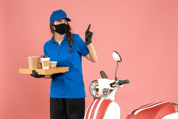 Vista dall'alto della ragazza del corriere emotivo che indossa guanti con maschera medica in piedi accanto alla moto con in mano piccole torte di caffè rivolte verso l'alto su sfondo color pesca pastello