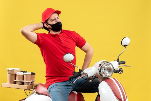 Vista dall'alto del ragazzo di corriere emotivo che indossa guanti di camicetta e cappello rossi nella mascherina medica che consegna l'ordine che si siede sullo scooter che si sente confuso