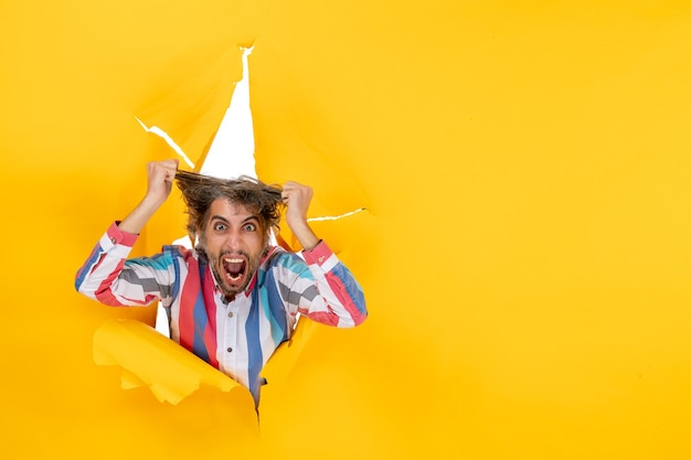Top view of an emotional and exhausted young guy through a torn hole in yellow paper