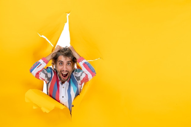 Top view of an emotional overtired and exhausted young guy through a torn hole in yellow paper