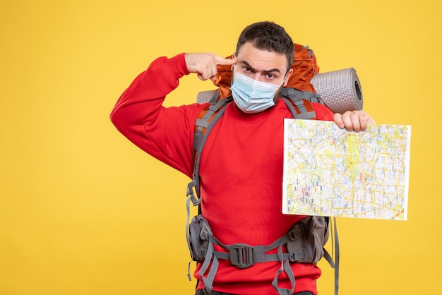 Top view of an emotional thoughtful traveller guy wearing medical mask with backpack holding map on yellow background
