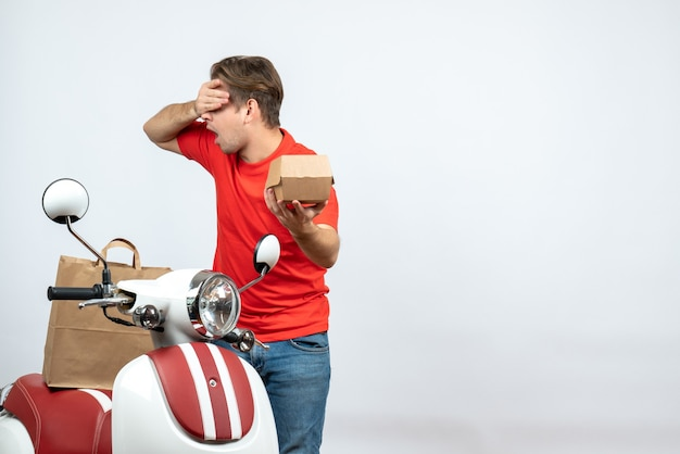 Top view of emotional tired delivery guy in red uniform standing near scooter holding order on white background
