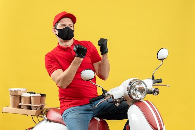 Vista dall'alto del giovane adulto emotivo che indossa la camicetta rossa e guanti del cappello nella mascherina medica che trasporta l'ordine che si siede sullo scooter che si sente arrabbiato