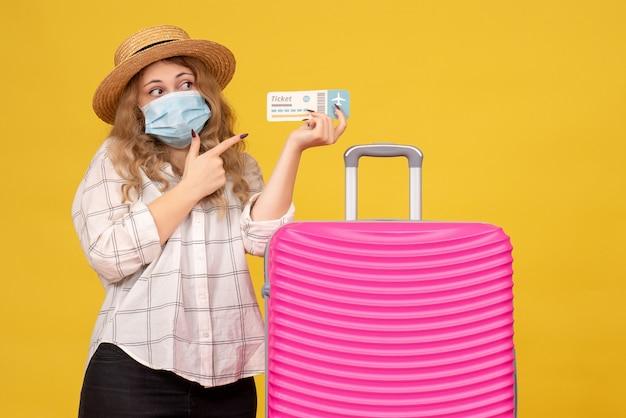 Vista dall'alto della giovane donna emotiva che indossa la maschera che indica biglietto e in piedi vicino alla sua borsa rosa