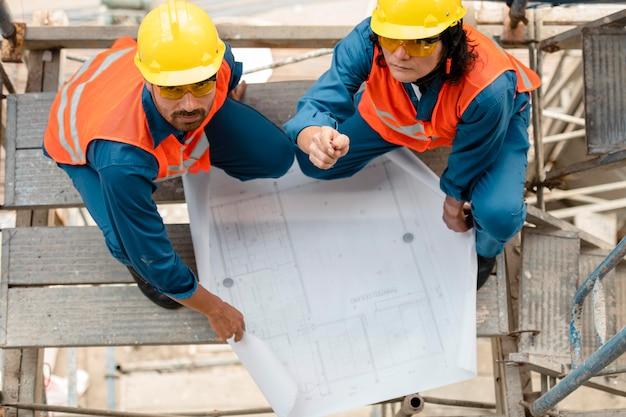 Вид сверху сотрудников с оборудованием для обеспечения безопасности