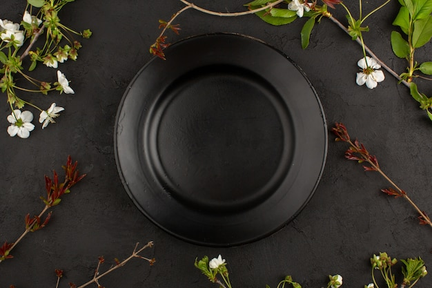 Top view empty black plate along with white flowers on the dark floor