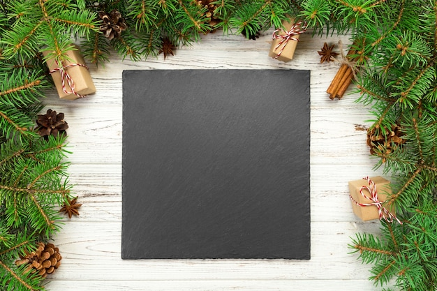 평면도. 나무 크리스마스 배경에 빈 검은 슬레이트 사각형 접시. 새해 장식이 있는 휴일 저녁 식사 요리 개념.