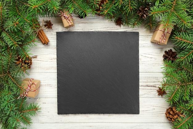 평면도. 나무 크리스마스 배경 빈 검은 슬레이트 사각형 접시. 새해 장식 휴일 저녁 식사 요리