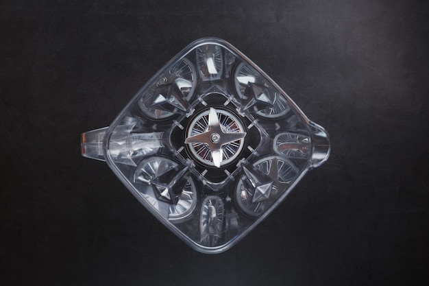 Top view of an empty blender bowl with blades on a black surface