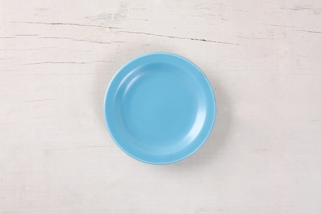 Top view of empty blue plate put on white wood table with space for copy.