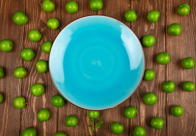 Top view of an empty blue plate and sour green plums arranged around on wooden table