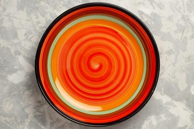Вид сверху на пустую яркую тарелку из оранжевого цвета на белой поверхности