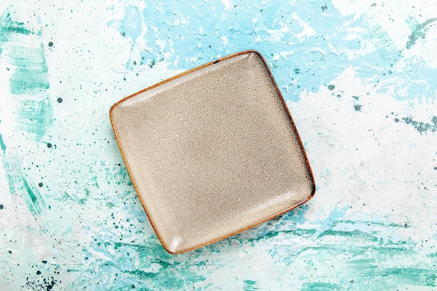 Top view empty brown plate square formed on blue background kitchen food plate cutlery