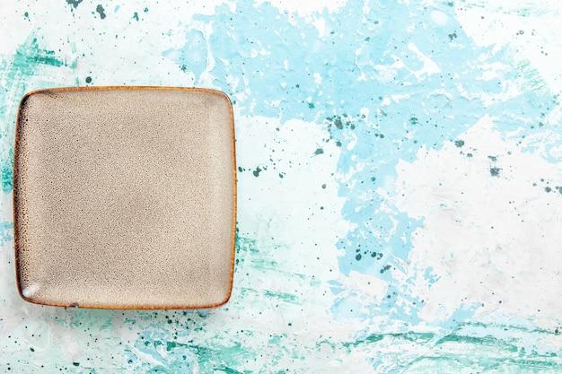 Вид сверху пустая коричневая квадратная тарелка, образованная на голубом столе, кухонная тарелка для еды, столовые приборы