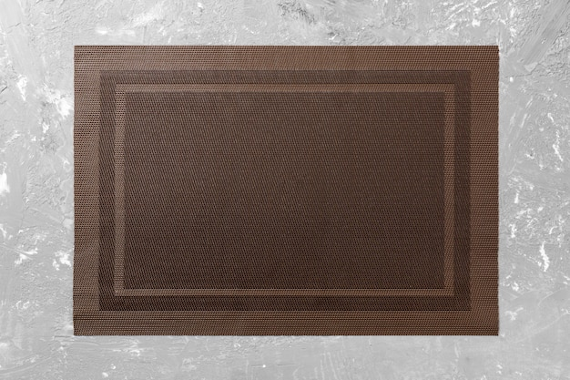 Top view of empty brown tablecloth on cement background with copy space