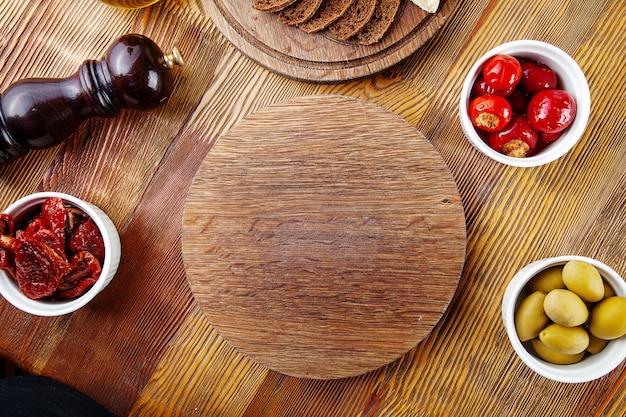 Вид сверху пустая разделочная доска для пиццы или мяса. пустая доска для подачи пищи в составе с, вяленые помидоры, брускетта и посуда на деревянных фоне. плоская планировка